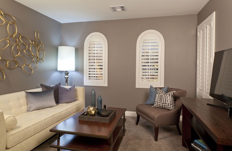 Plantation shutters on arched windows in neutral colored family room