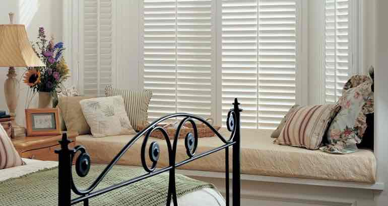 Polywood shutters in a chic bedroom bay window.