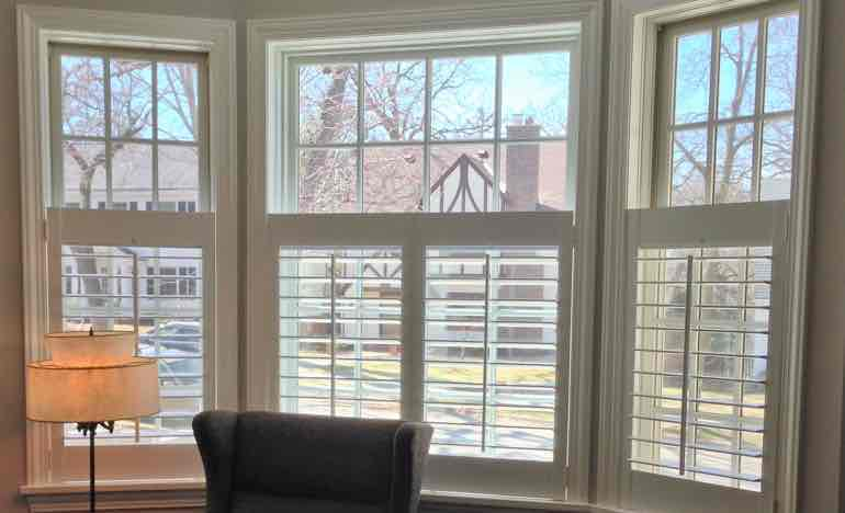 Half-length plantation shutters in living room bay window.