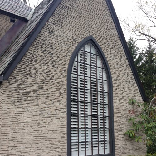 outdoor view of brick home with plantation shutters