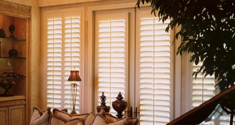 Plantation shutters on french door and window in Gainesville parlor