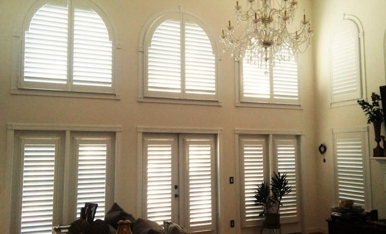 Television room in open concept Gainesville home with plantation shutters on high windows.