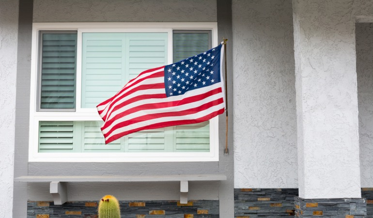 Alt Text: American flag flying in front of a home
