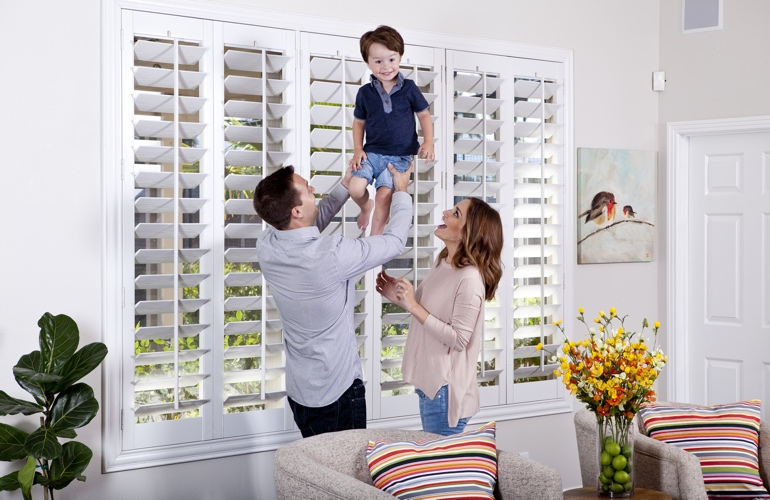 Parents with toddler in front of plantation shutters