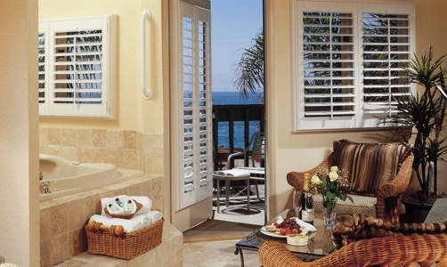 Plantation shutters on casement windows in a oceanfront room.