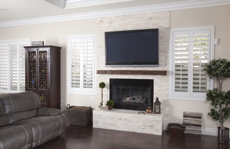 White plantation shutters in a Gainesville living room with dark hardwood floors.