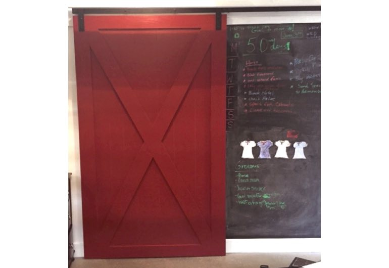Red x-frame barn door with black hardware next to chalkboard