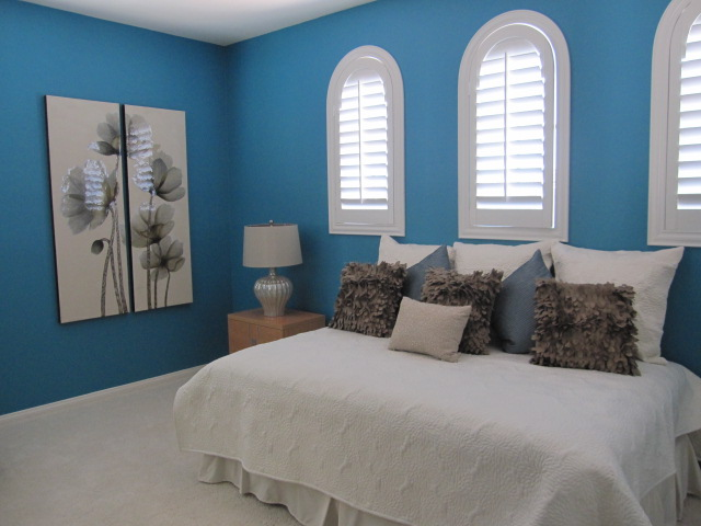 Blue bedroom with arched white shutters.