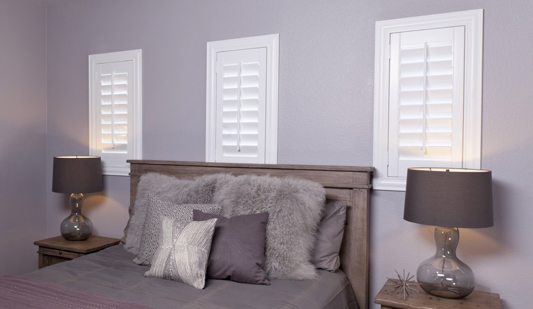 White plantation shutters in Gainesville bedroom windows.