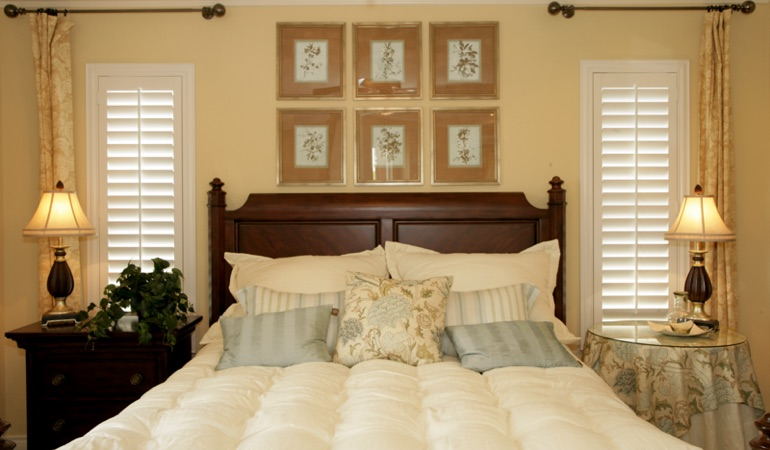 Beige bedroom with white plantation shutters covering windows in Gainesville
