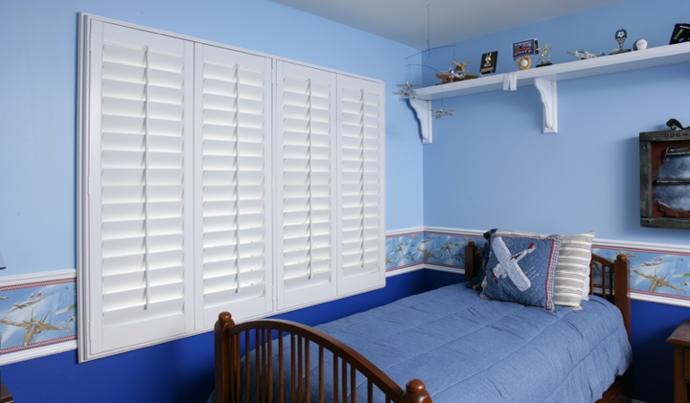 Blue kids bedroom with white plantation shutters in Gainesville